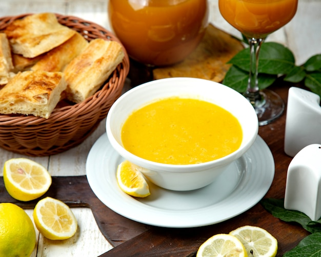 Sopa de lentejas en un tazón blanco y una rodaja de limón