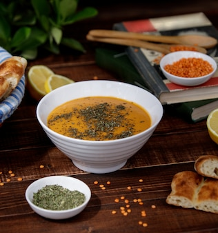 Sopa de lentejas y tomate con hierbas en un tazón blanco