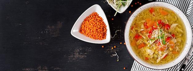 Sopa con lentejas, zanahorias, carne de pollo, pimentón, apio en un tazón.