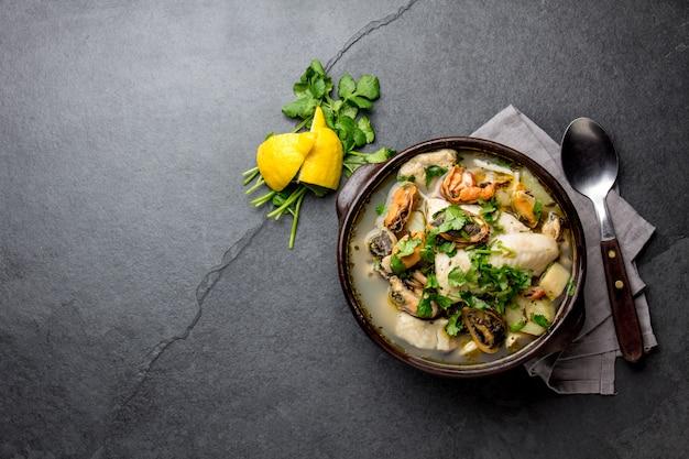Sopa de mariscos en cuenco de arcilla sobre pizarra gris
