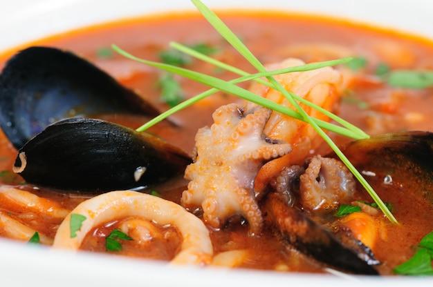 Sopa de mariscos en primer plano de plato blanco