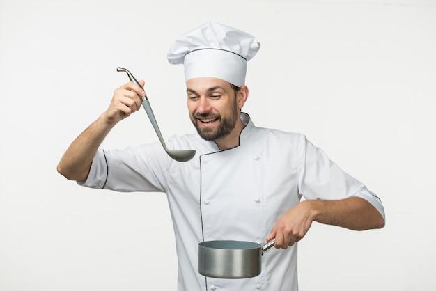 Sopa masculina de la prueba del cocinero en cucharón contra el fondo blanco