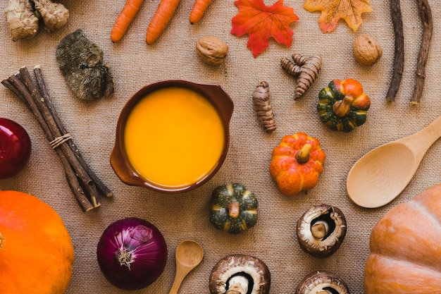Sopa en medio de verduras y cucharas