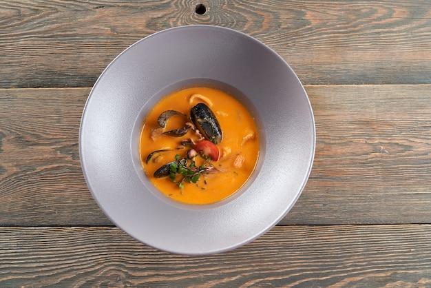 Sopa de mejillones y naranja en restaurante.