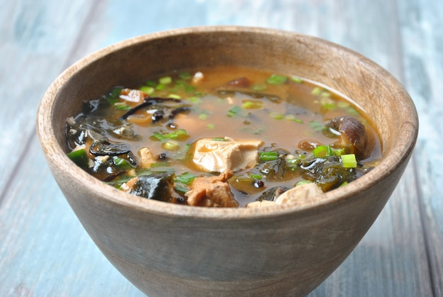 Sopa de miso japonesa con atún fresco, algas secas, tofu, hongos secos shiitake en un recipiente de madera en el fondo de madera