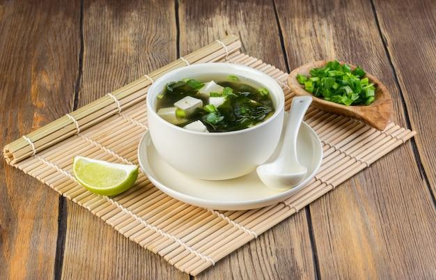Sopa de miso japonesa en un cuenco blanco en la tabla cubierta con la estera de bambú. copia espacio