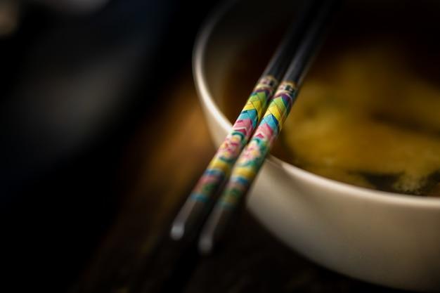 Sopa de miso en un tazón blanco con palillos
