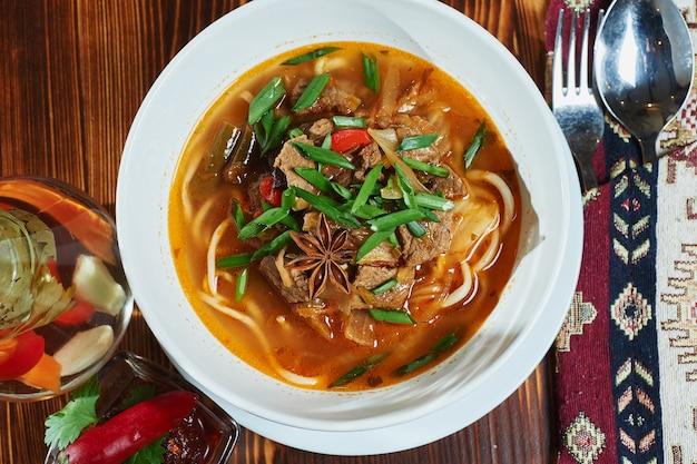 Sopa oriental uzbeka lagman en una mesa de madera.