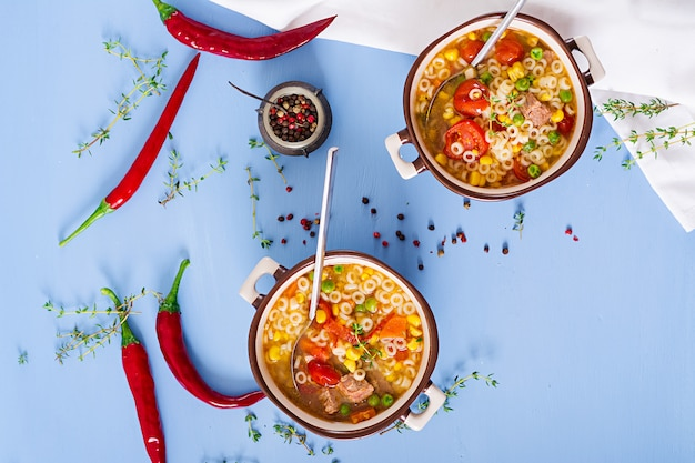 Sopa con pasta pequeña, verduras y trozos de carne en un recipiente en la mesa azul. comida italiana.