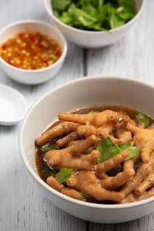 Sopa de patas de pollo guisada servida con salsa de pescado picante