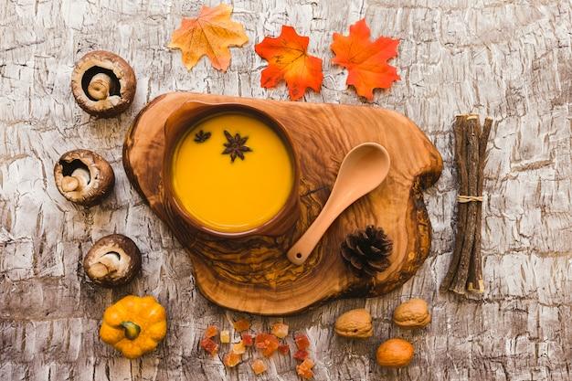 Sopa en pedazo de madera cerca de símbolos de otoño