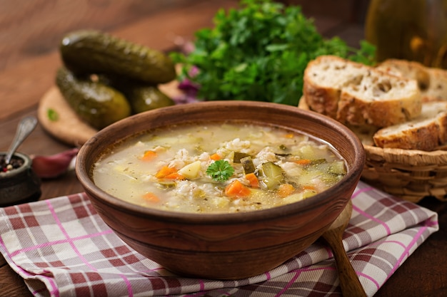 Sopa con pepinos conservados en vinagre y cebada de perla - rassolnik en un fondo de madera.