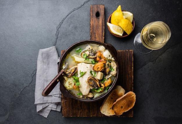 Sopa de pescado y marisco en cuencos de arcilla servida con vino blanco frío.