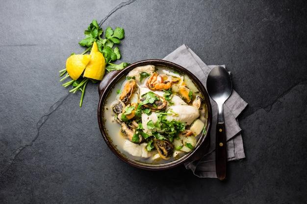 Sopa de pescado y marisco en cuencos de barro servido con limón y cilantro.