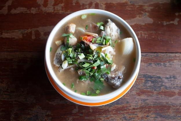Sopa de pescado picante aromatizada con limoncillo y lima servida en una mesa de madera