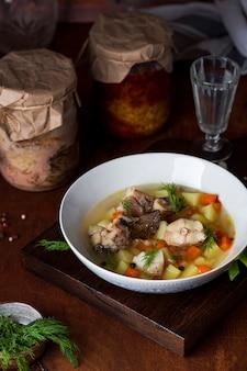 Sopa de pescado rústica en un recipiente sobre un fondo de madera