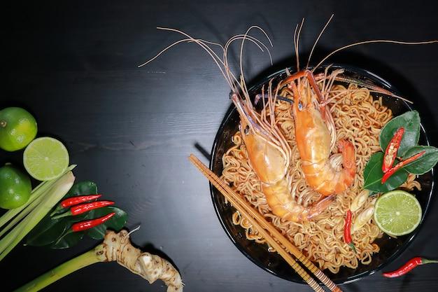 Sopa picante de fideos instantáneos con camarones de ríos en la parte superior, nombre tom yum kung en thailand foods style.