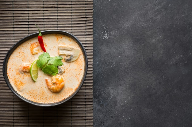 Sopa picante tailandesa de tom yam kung con camarones, mariscos, leche de coco y ají. copia espacio