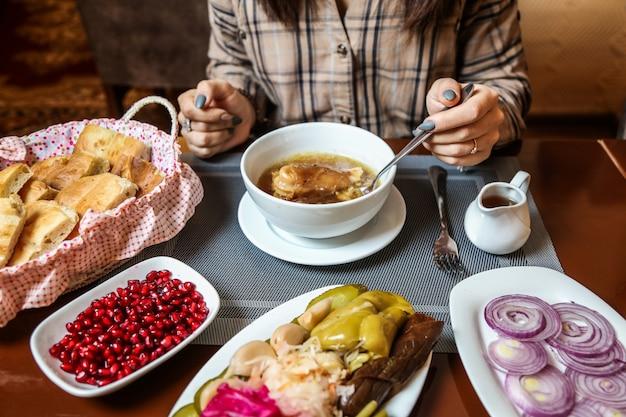 Sopa piti tradicional con carne de cordero y verduras y aperitivos vista lateral
