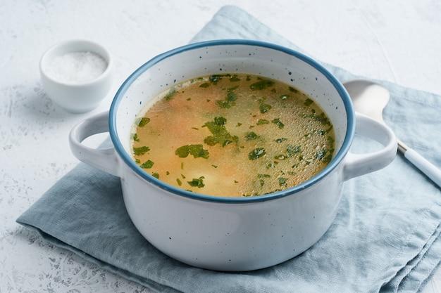 Sopa de pollo, comida casera escandinava con mesa de piedra azul, vista lateral