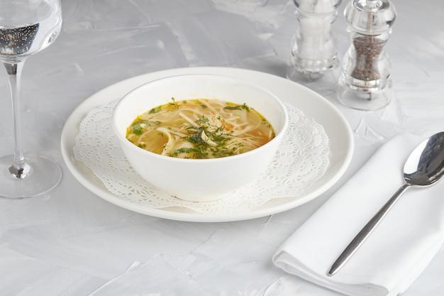Sopa de pollo con fideos, servicio de restaurante, fondo claro