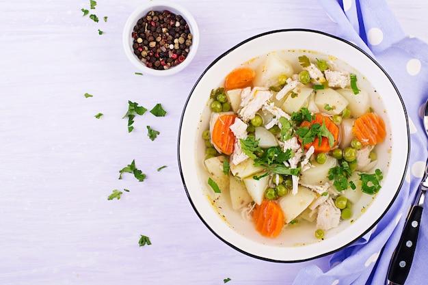 Sopa de pollo con guisantes verdes, zanahorias y papas en un tazón blanco sobre una luz, vista superior