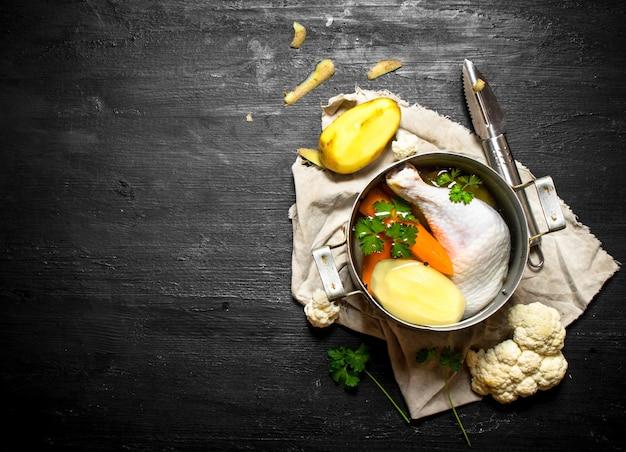 Sopa de pollo con patatas, zanahorias y especias. sobre un fondo de madera negra.