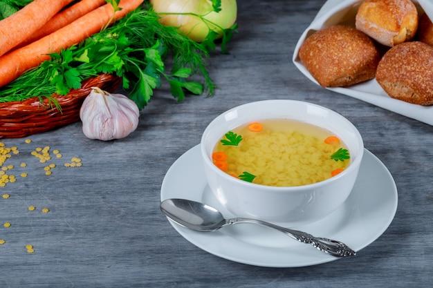 Sopa de pollo en tazón de caldo y verduras frescas