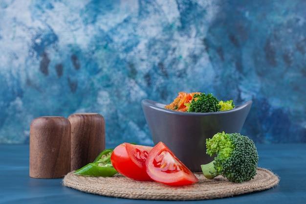 Sopa de pollo en un tazón y verduras en rodajas sobre un salvamanteles sobre la superficie azul