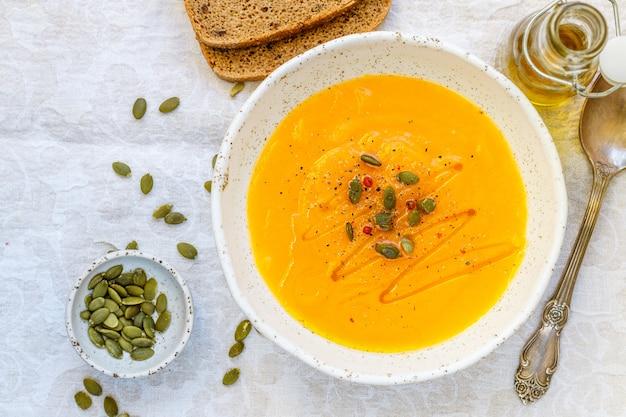 Sopa de puré de calabaza y zanahoria con semillas, pimienta rosa y aceite de oliva.