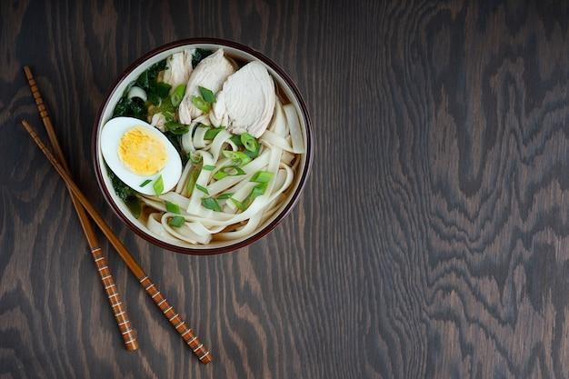 Sopa de ramen asiática hecha de caldo de pollo en un recipiente junto con palillos. vista superior