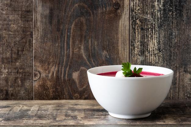 Sopa de remolacha en un tazón blanco sobre mesa de madera copia espacio