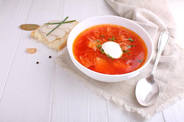 Sopa roja del borscht en el cuenco blanco con la crema agria y el perejil, visión superior, en fondo blanco de madera.