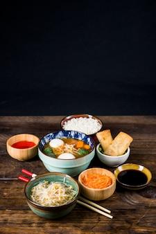 Sopa tailandesa de bolas de pescado; rollitos de primavera; brotes de frijoles y salsa con palillos en el escritorio de madera con fondo negro