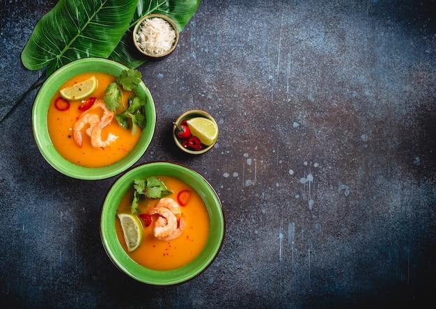 Sopa tailandesa saludable tradicional tom yum con camarones, limón, cilantro en un tazón sobre fondo rústico con arroz blanco, fotografía cenital. concepto de auténtica comida tailandesa con espacio de copia