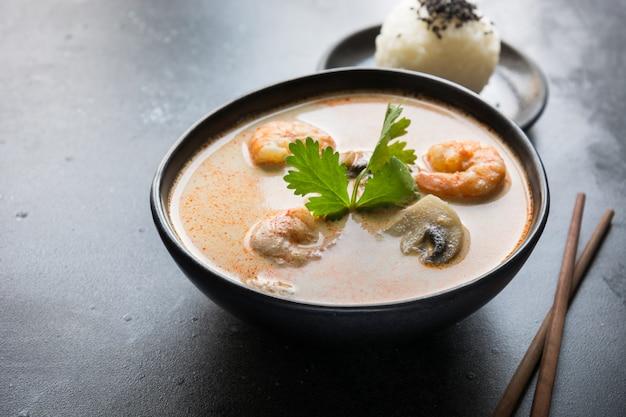 Sopa tailandesa de tom yam kung con camarones, mariscos, leche de coco, ají y arroz.