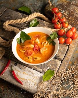 Sopa tom yam con camarones, calamares y pimientos picantes en una tabla de madera con textura