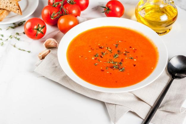 Sopa de tomate con aceite de oliva y hierbas, con pan tostado, sobre mármol blanco, copyspace