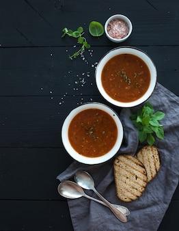 Sopa de tomate asado con albahaca fresca, especias y pan en cuencos de metal rústico sobre mesa negra