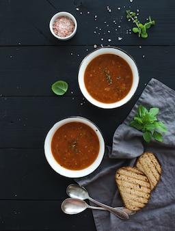 Sopa de tomate asado con albahaca fresca, especias y pan en cuencos de metal rústico sobre superficie negra