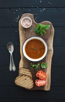 Sopa de tomate asado con albahaca fresca, especias y pan en un recipiente de metal vintage sobre tabla de madera sobre mesa negra