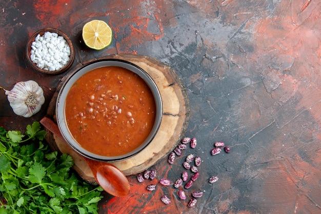 Sopa de tomate en una cuchara de tazón azul en bandeja de madera, sal de ajo y limón, un manojo de verde en metraje de mesa de colores mezclados