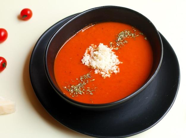 Sopa de tomate y hierbas con queso encima