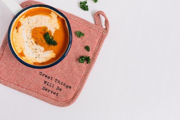 Sopa de tomate en mantel sobre fondo blanco