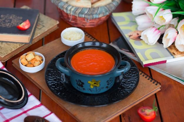 Sopa de tomate en una olla con queso parmesano picado y galletas de pan.