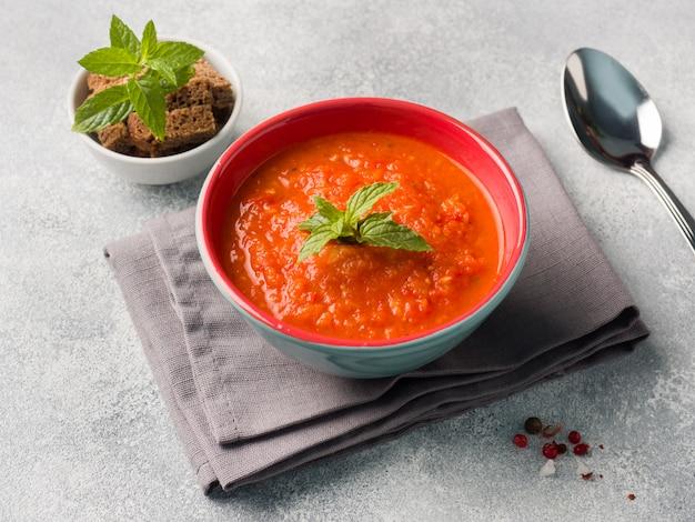 Sopa de tomate en un tazón de cerámica sobre una servilleta con rebanadas de pan tostado