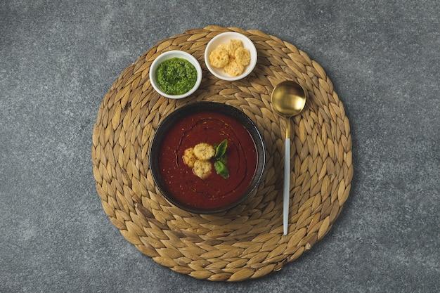 Sopa de tomate en un tazón negro sobre una mesa de piedra gris