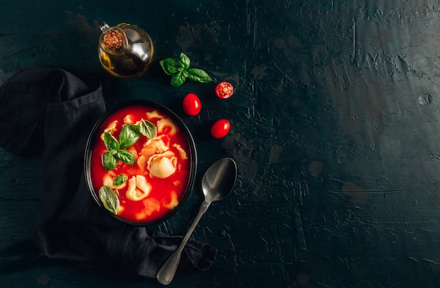 Sopa de tomate con tortellini en un tazón negro sobre fondo oscuro.