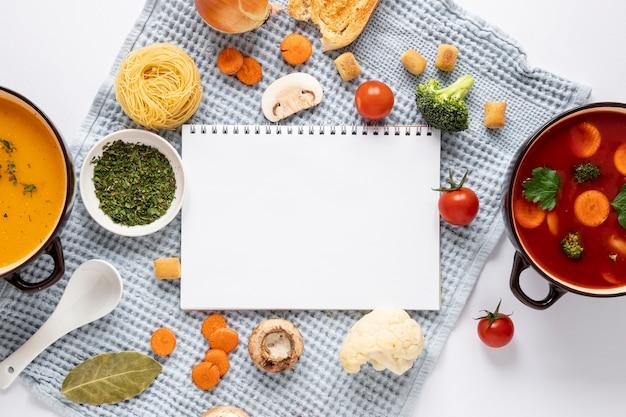 Sopa de tomate y verduras con bloc de notas vacío