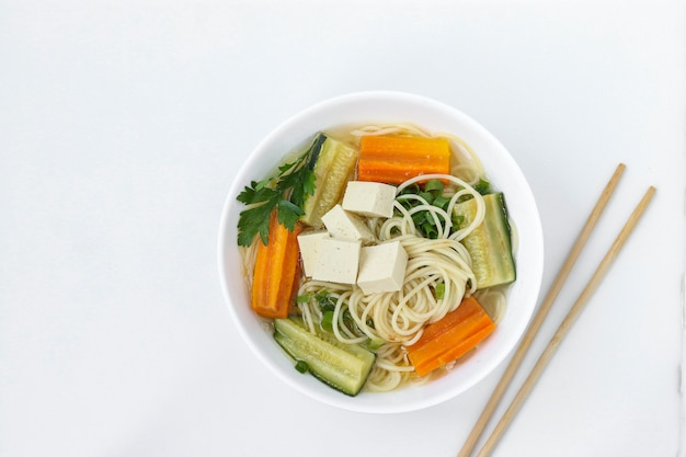 Sopa tradicional asiática con queso tofu, fideos, zanahorias y calabacín sobre fondo blanco.